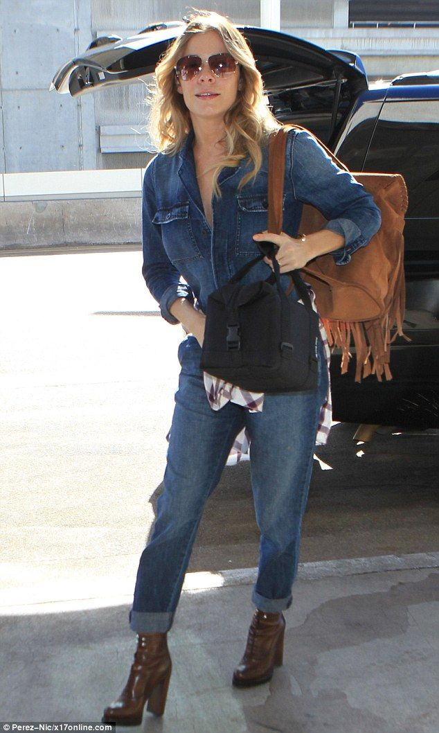 Country cutie: The blonde beauty was airport ready in her boyfriend jean jumpsuit. She cinched in her already tiny waist with a maroon and white plain shirt