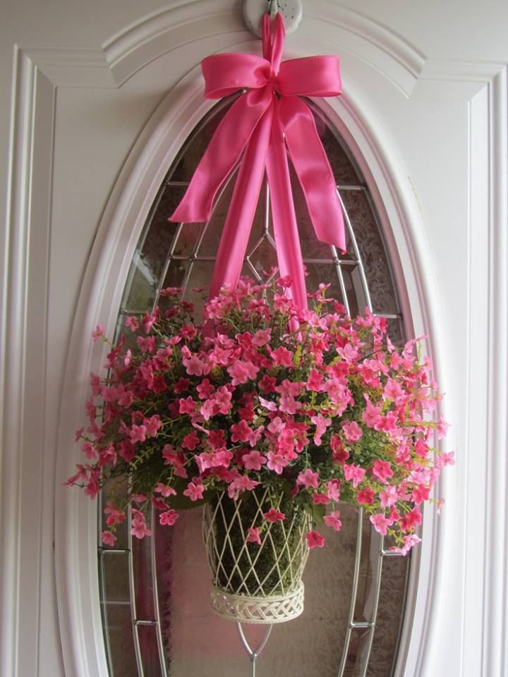 Basket of flowers hung from a ribbon on glass window front door