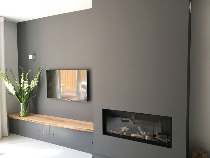 Grijs gecombineerd met hout, extra zit mogelijkheid met opbergruimte in tv en haard wand.