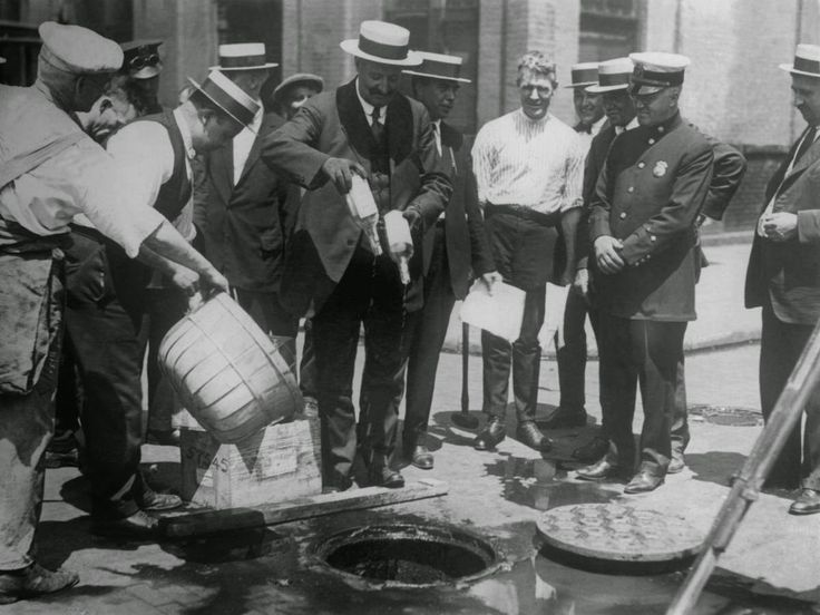 "The Eighteenth Amendment of the United States Constitution, prohibiting the production and selling of ""intoxicating liquors,"" had been ratified in 1919, and the Volstead Act was enacted in order to enforce and regulate the Amendment. Here, alcohol seized by police is dumped into sewage drains in New York."