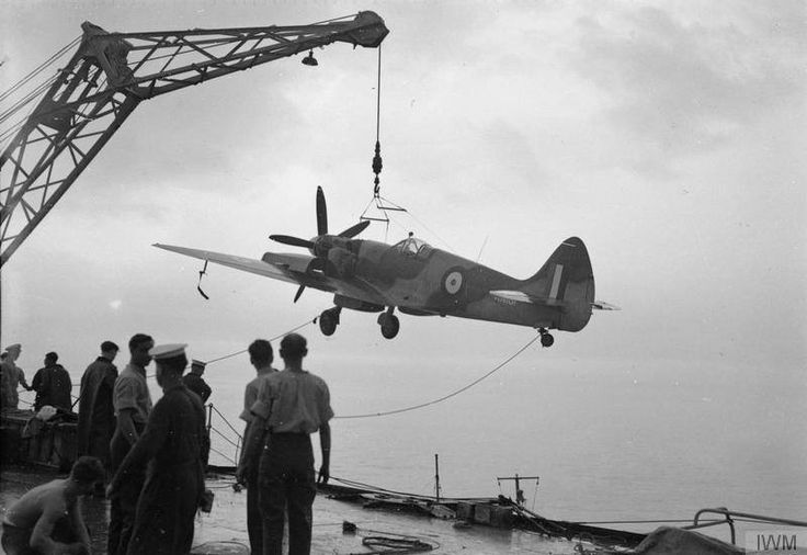 A Spitfire XIV of No.17 Sqn RAF being unloaded from the aircraft carrier HMS VENGEANCE at Iwakumi, Japan. ready for service with the British Commonwealth Air Forces of Occupation. April 1946. (IWM)