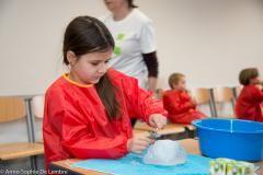 De kinderen onderzoeken op welke manier en met welke materialen ze grote ijsblokken gemakkelijk in stukken kunnen breken.