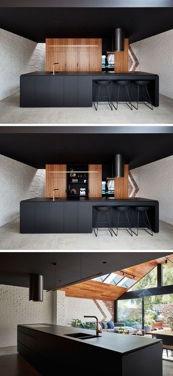 This modern kitchen features a black island and ceiling, and wood cabinets.