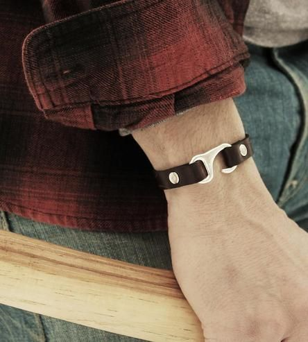 Striking in leather and brass, this hook bracelet makes a bold statement on wrists. The leather bracelet is made from sturdy bridle leather and riveted with metal accents for durability. It's finished with a hook closure, to easily put it on and take off. The cuff also features hand carved detailing, making each bracelet one of a kind.