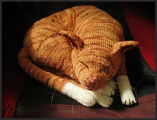 "Jingga (means ""orange"" in Indonesian) was knitted in self-striping yarn to resemble the tabby pattern. To achieve a smooth stripe pattern and minimize seam, the main body was knitted one-piece in the round from the back right leg to the snout."