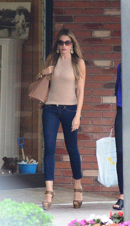 Skinny jeans showing ankle, high heels, big bag and big earrings.