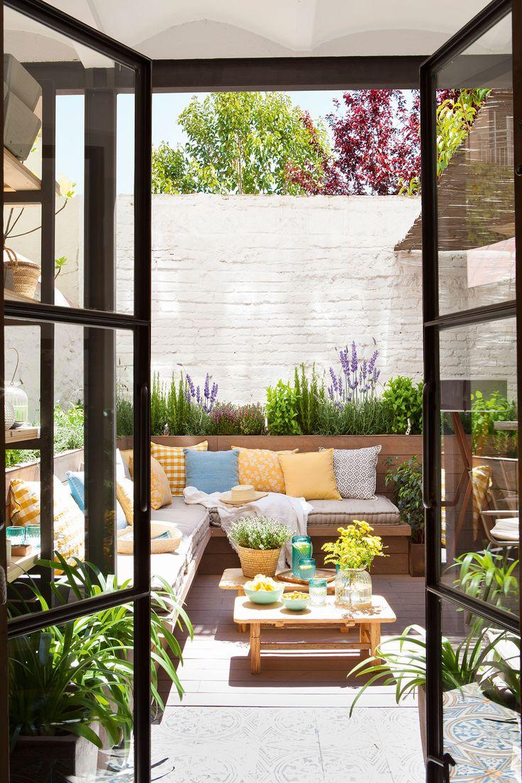 """Terraza vista desde el salón con gran sofá en """"L"""" de obra"""