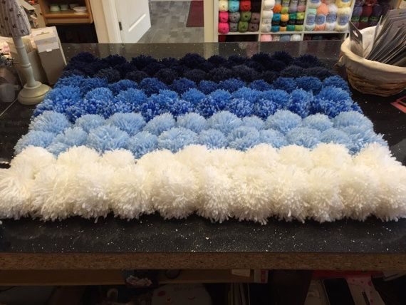 Pom Pom rug in shades of blue. Rug is 17 by 27 inches. The rug is not suitable for machine washing.  Other colours will be available soon. But you can