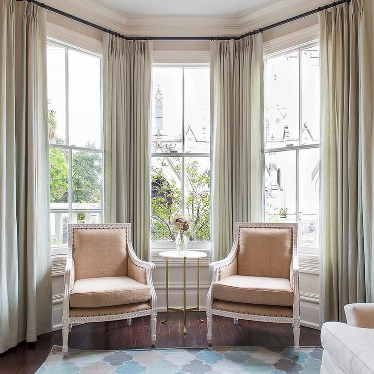 sophisticated sitting room features a bay window dressed in gray green drapes filled with beige bergere chairs and a round marble and brass table atop wood