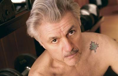 John Irving shows off his tattoo.