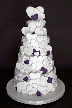 For the true romantic at heart, a four tier white and purple wedding cake decorated with lots of white and purple edible heart shaped sugar paste hearts of different sizes. From www.flickr.com Scrumptious Cakes ........   #wedding #cake #birthday