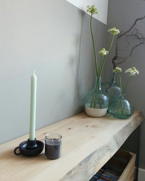 Mijn stoere wandplank van oud iepenhout met daarop een kandelaar en kaarsen van Hema en een paar glazen flesvazen. IG @marielmulder