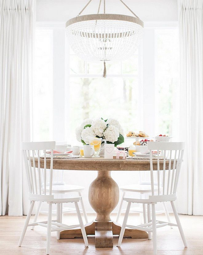 fabulous simple and elegant but impactful chandelier over simple timber dining table and white chairs