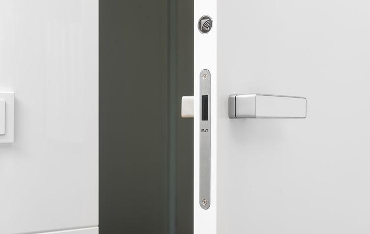 Realizace interiéru. Minimalisticky zařízený interiér s bílou lakovanou kuchyní v moderním designu a navazujících bílých dveří Millenium do obkladu.