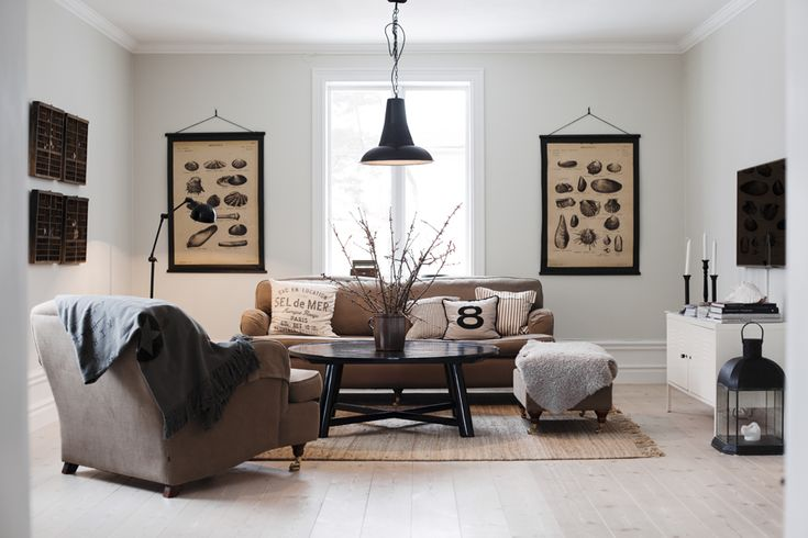 Vardagsrum med Howardsoffa– och fåtölj från Posh living. Golvlampa och taklampa från Olsson & Jensen. Soffbord från Housedoctor, matta och kuddar Day home. Planscher och tavlor från auktioner och loppisar.