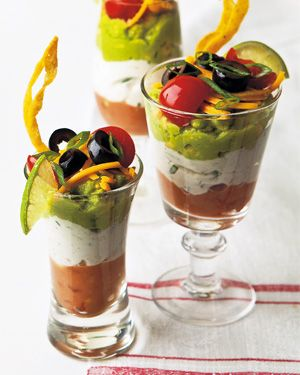 Fun Mexican Party Appetizers served in individual parfaits with bean, sour cream and guacamole layers and topped with cheese, tomato and black olives!  Yummy!