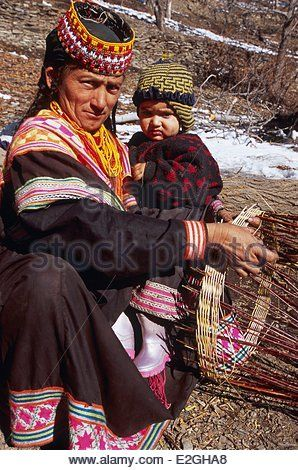Pakistan Khyber Pakhtunkhwa Kalash valleys Bumburet valley Kalash woman working traditional basket work with a child - Stock Photo