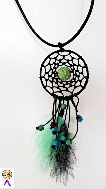 ŁAPACZ SNÓW. Obręcz oraz sieć w kolorze czarnym. W środku znajduje się zielona imitacja korala. Dół wykończony piórami marabuta i zawieszonymi na sznurku kolorowymi koralikami.