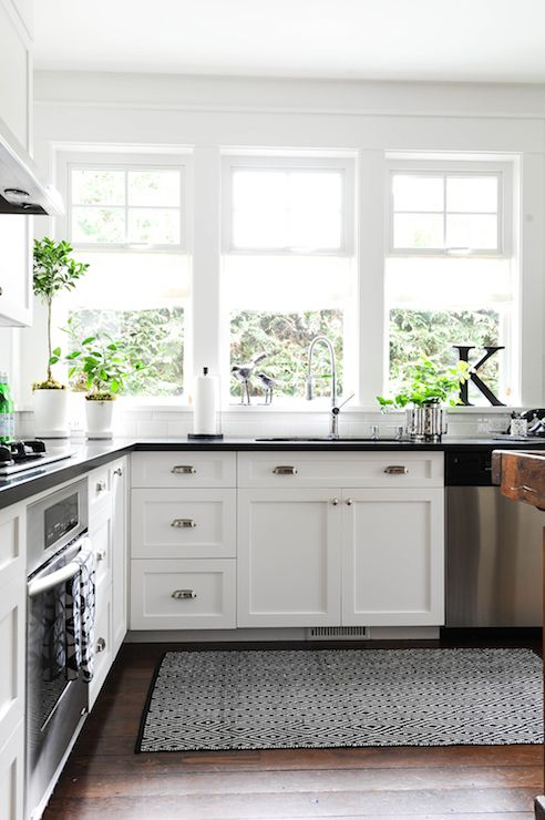Black and white kitchen features white shaker cabinets accented with cup pulls and topped with black countertops and subway tiled backsplash. Bank of windows dressed in white roller shades over kitchen sink paired with instant hot water faucet alongside black and white diamond rug.