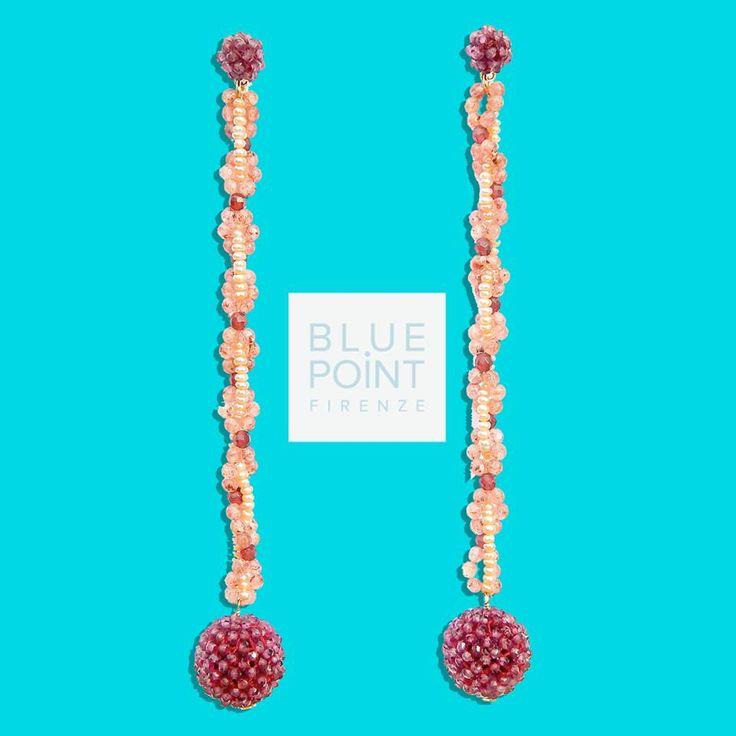 Orecchini Strawberry Balls  Le sfere di granato, formate da tante piccole pietre perfette ed omogenee nel calibro e nel colore sono cucite tutte a mano in una lavorazione che, a Torre del Greco (Napoli), si tramanda dai primi anni del '900. La catena d'oro che unisce i due estremi degli orecchini è ricoperta da un intreccio di perline d'acqua dolce e quarzo rosa strawberry.