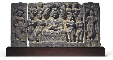 A gray schist relief with the offering of the four bowls  Gandhara, 2nd/3rd century  Well carved with Buddha at center flanked by pairs of attendants offering bowls, with further Bodhisattvas in adoration at the back and flanked female attendants beneath Ashoka trees on separately carved panels 13¼ x 26 3/8 in. (33.5 x 67 cm.)