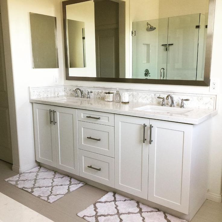 Two white and gray trellis bath mats from Target stand before a white dual shaker bath vanity adorned with satin nickel pulls and topped with a white quartz countertop that resembles white marble fitted with his and her sinks.