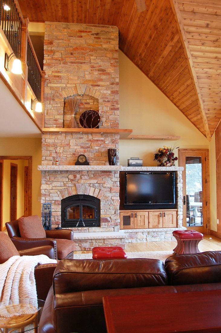 Stone tall fireplace with arched niche wood and stone floating shelving entertainment center with