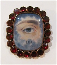on Hill Country House | a blue-grey lover's eye brooch with a garnet surround | the clouds indicate that the subject is deceased