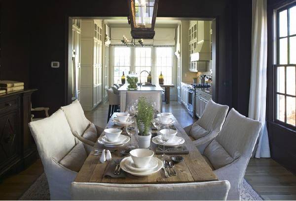 Beautiful cottage dining room design with rustic wood dining table with slip-covered canvas dining chairs! Love the black lantern pendant lighting in this dining room! Black paint wall color. Black dining room! black gray beige brown tan dining room colors.