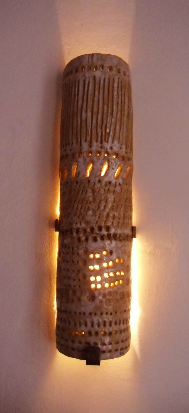 Ceramic wall lamp hold with an iron structure, by Elena Gutierrez Giulianotti.