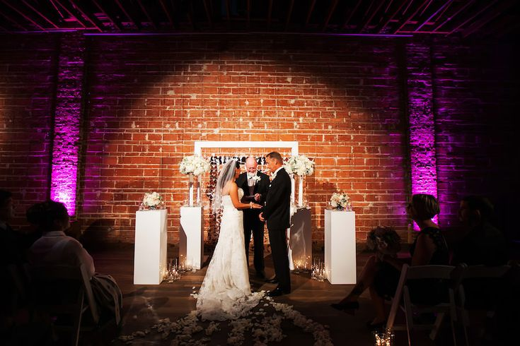 Bride and Groom Exchanging Vows at Indoor, Wedding Ceremony with Exposed Brick Walls and Purple Uplighting | Modern Wedding Ceremony Ideas | St. Petersburg Wedding Venue NOVA 535 | Wedding Photographer Limelight Photography