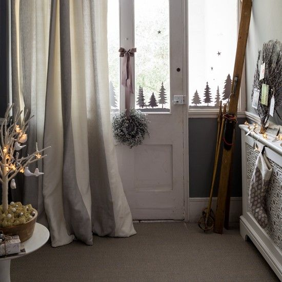 Christmas hallway with grey painted walls, white radiator cover and paper tree decorations