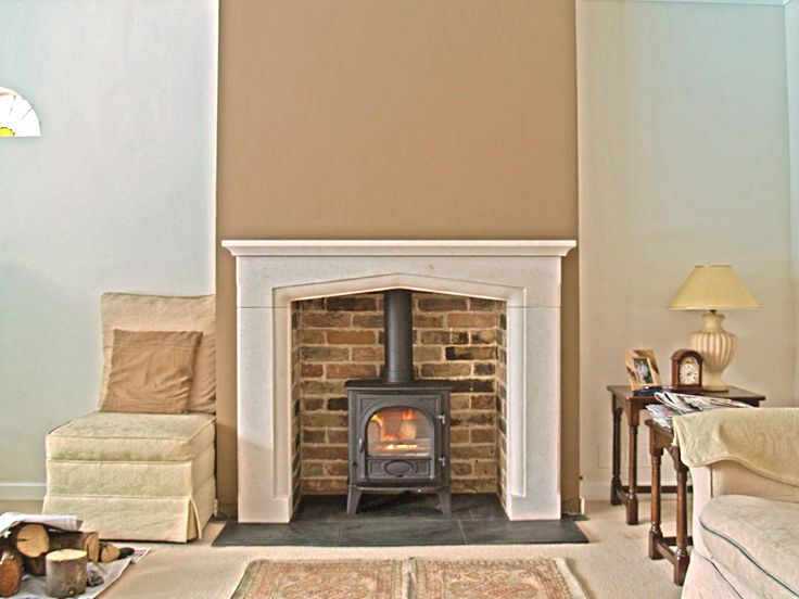 bespoke portugese solid limestone mantel with reclaimed brick slip chamber natural slate tiled hearth and wood stove fitted in hockley esse