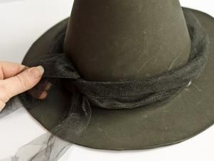 To embellish the witch's hat, tie a reserved piece of tulle around it. Secure the tulle with a simple knot in the back, held in place with a dab of hot glue.