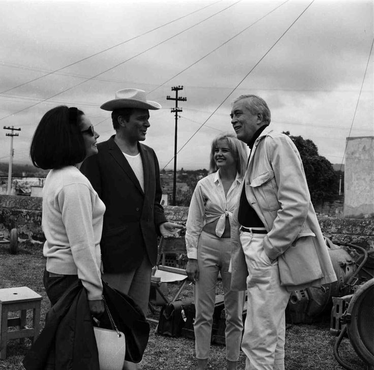 Medium BTS shot of Elizabeth Taylor standing near husband Richard Burton who plays Rev. Dr. T. Lawrence Shannon, wearing cowboy hat, Sue Lyon who plays Charlotte Goodall and director John Huston.