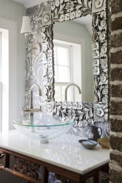 An intricate mirror hung atop paisley-patterned wallpaper