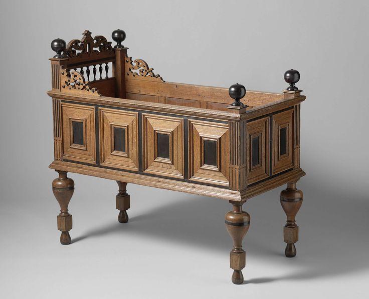 Anonymous | Child's cot, Anonymous, c. 1620 - c. 1650 | Kinderledikant van eikenhout, versierd met ebben. Het meubel rust op vaaspoten. De zijschotten hebben vier, de eindschotten tweepanelen binnen profiellijsten en met ebben spiegels in het middenveld. De stijlen zijn doorgetrokken en worden bekroond door ebben ballen; die aan het hoofdeind gaan hoger door. Tussen deze beide stijlen is een regel gevoegd met een bekroning van opengewerkt rolwerk, bezet met ebben dopjes. De regel wordt…
