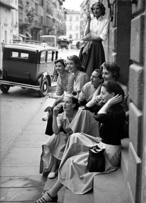 Fashion models rest on a street corner, by Milton Greene, Italy, 1951.