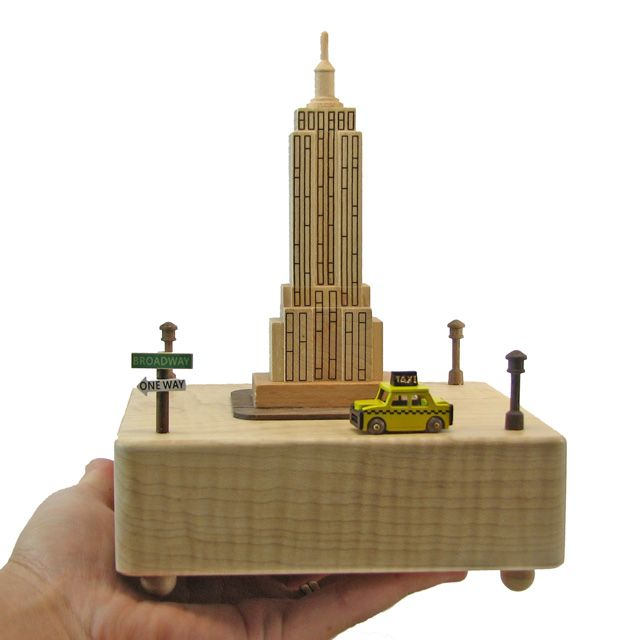 """This unique fine wood crafted music box comes with a miniature yellow taxi that circles around the Empire State Building according to the rhythm of the music """"De Camptown Race"""" by Stephen Foster. Than"""
