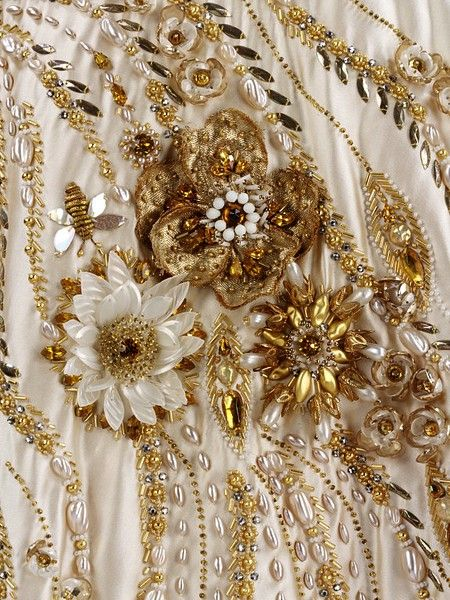 Lavish gold and white beadwork encrusts this ivory evening dress worn by Queen Elizabeth II on a state visit to Paris in 1957.