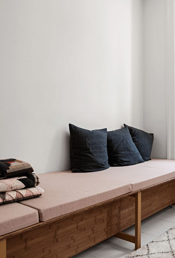 Minimal mattress sofa in dusty pink and three of the same cushion covers photo by Peter Kragballe
