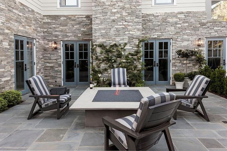 Blue framed french doors lead to a gorgeous patio boasting an oversized square concrete gas fire pit surrounded by dark gray Adirondack chairs topped with white and blue striped seat cushions and sat upon shrub lined stunning slate pavers.