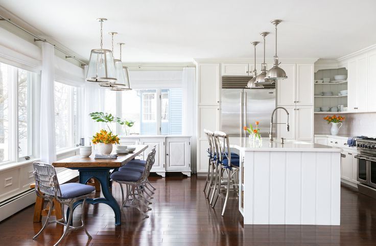 Beautiful kitchen features three Restoration Hardware Harmon pendants illuminate a shiplap clad island fitted with a sink and pull out faucet lined with metal x back counter stools lined with blue seat cushions.