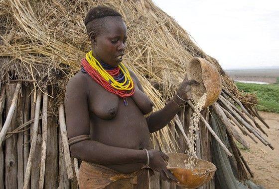 As casas da etnia Karo são circulares, construídas com troncos de madeira colocados lado a lado, sem nenhum barro nas paredes laterais, e levam um telhado de palha seca por cima. Uma jovem limpa grãos de sorgo. O cereal sorgo é um dos principais alimentos do povo Karo.  Fotografia: © Haroldo Castro / Época.  http://epoca.globo.com/colunas-e-blogs/viajologia/noticia/2015/06/isolados-no-sul-da-etiopia-os-karo-ainda-pintam-e-enfeitam-o-corpo.html