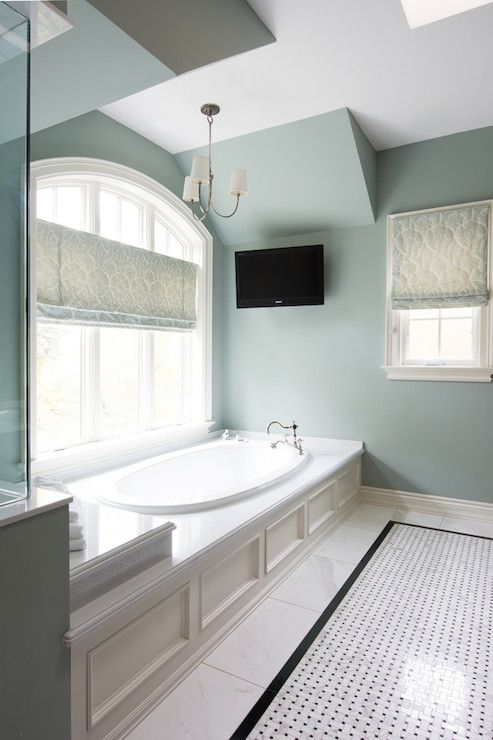 Incredible bathroom with oval drop-in bathtub accented with wainscoting paneled with hook spout faucet below arched window dressed with blue damask roman shade illuminated by a nickel chandelier with white shades.