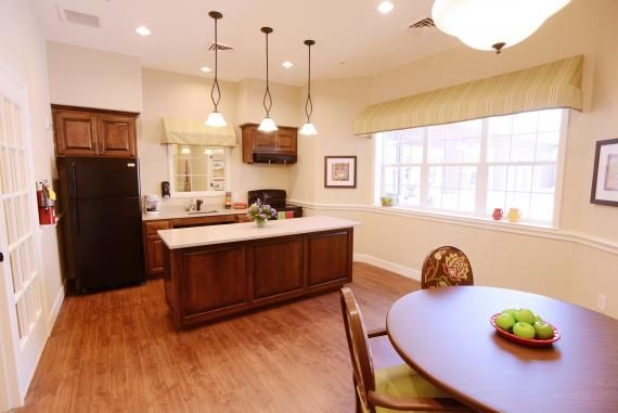 A lighter paint color was used in the ADA-compliant therapy kitchen to allow for natural light to reflect off the walls and create a brighter atmosphere. Safety features include rounded edges on the corners of the island and a shut-off lever in the cabinet above the stove so the stovetop or oven won't be turned on accidentally. Photo: The LaSalle Group; Randy Wilson Photography.