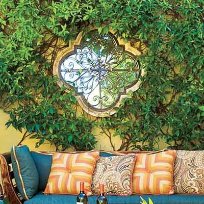 Hang a metal frame mirror on a garden wall. It makes it look like it is a window to another space