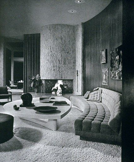 The living room of Mr. and Mrs. Eugene V. Klein's Trousdale Estates, Beverly Hills, residence. The room features a walnut paneled wall, custom tufted curved sofa, coffee table of picked cork and a large travertine fireplace. Interior design by Arthur Elrod. (Spring 1963) George R. Szanik, Leeland Lee, Fritz Taggari