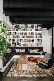 gorgeous loft! wood plank bench, L-sofa, leather moroccan poufs, danish modern armchair, shaggy moroccan style rug, industrial pendant lights, black ceiling, black-white-tan decor.
