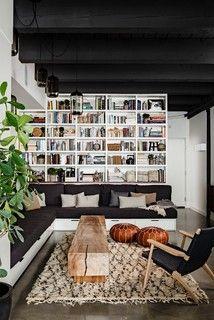 gorgeous loft! wood plank bench, L-sofa, leather moroccan poufs, danish modern armchair, shaggy moroccan style rug, industrial pendant lights, black ceiling, black-white-tan decor.